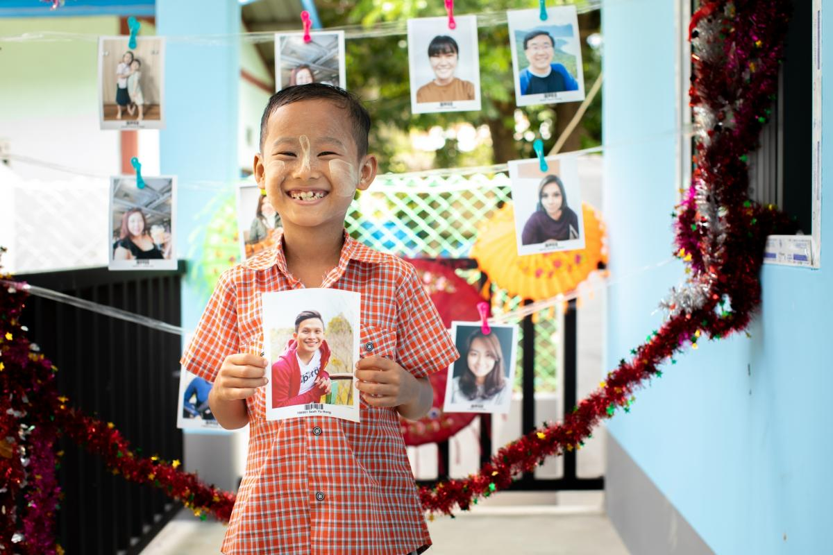 A child in Myanmar with the photo of a sponsor he has chosen