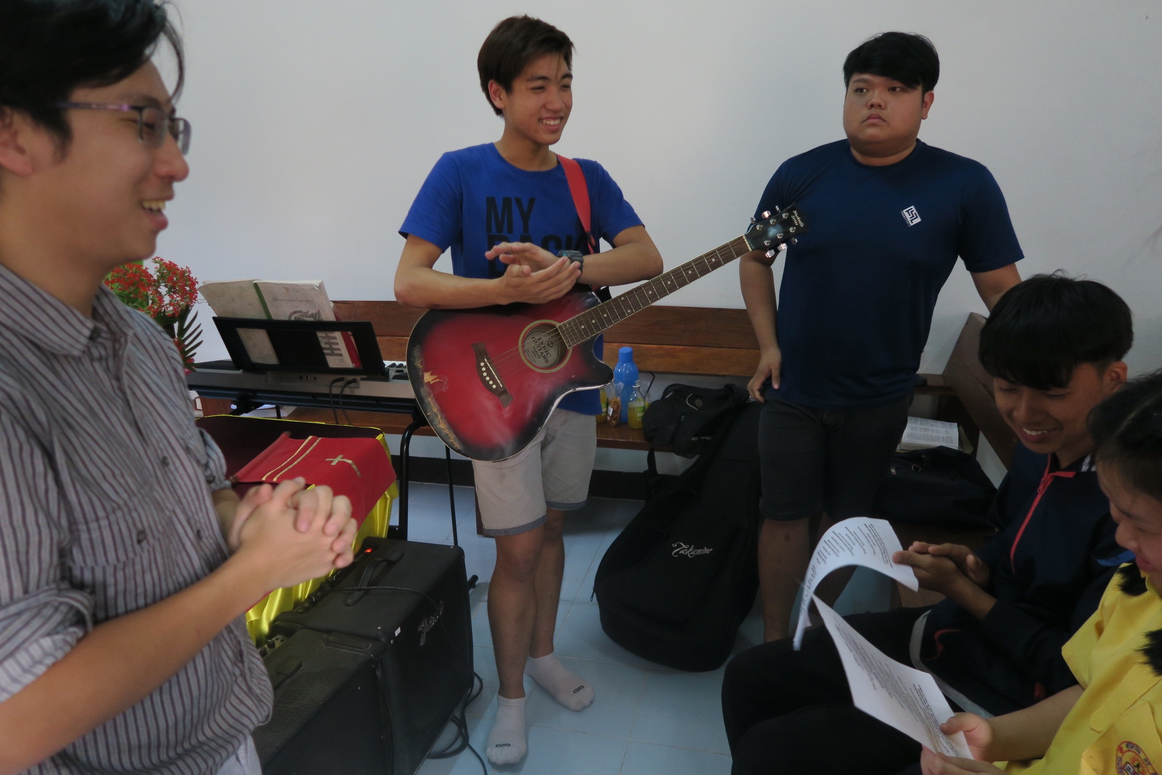 Teaching a song to a youth at a church.