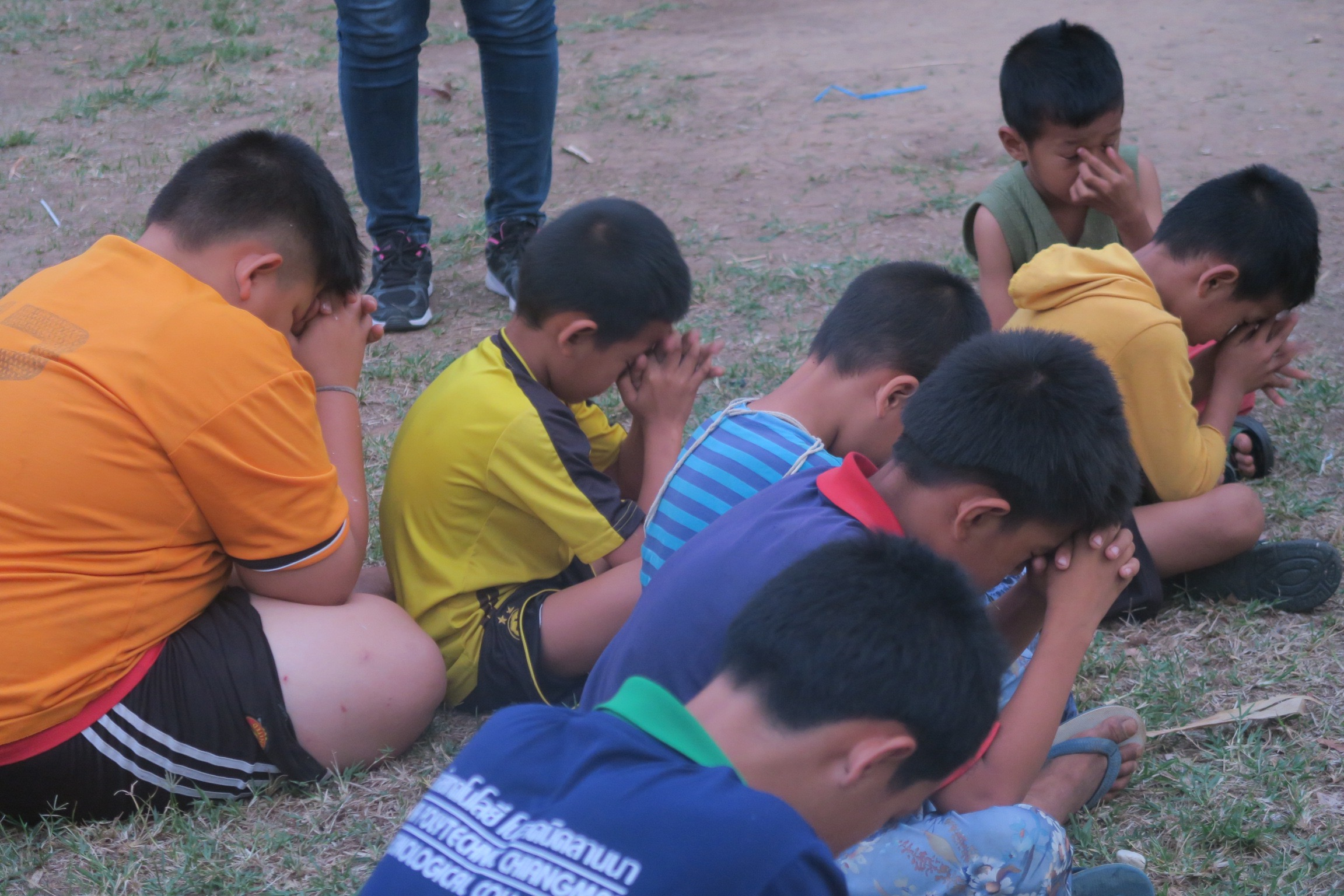 Children praying after a time of fellowship over football.