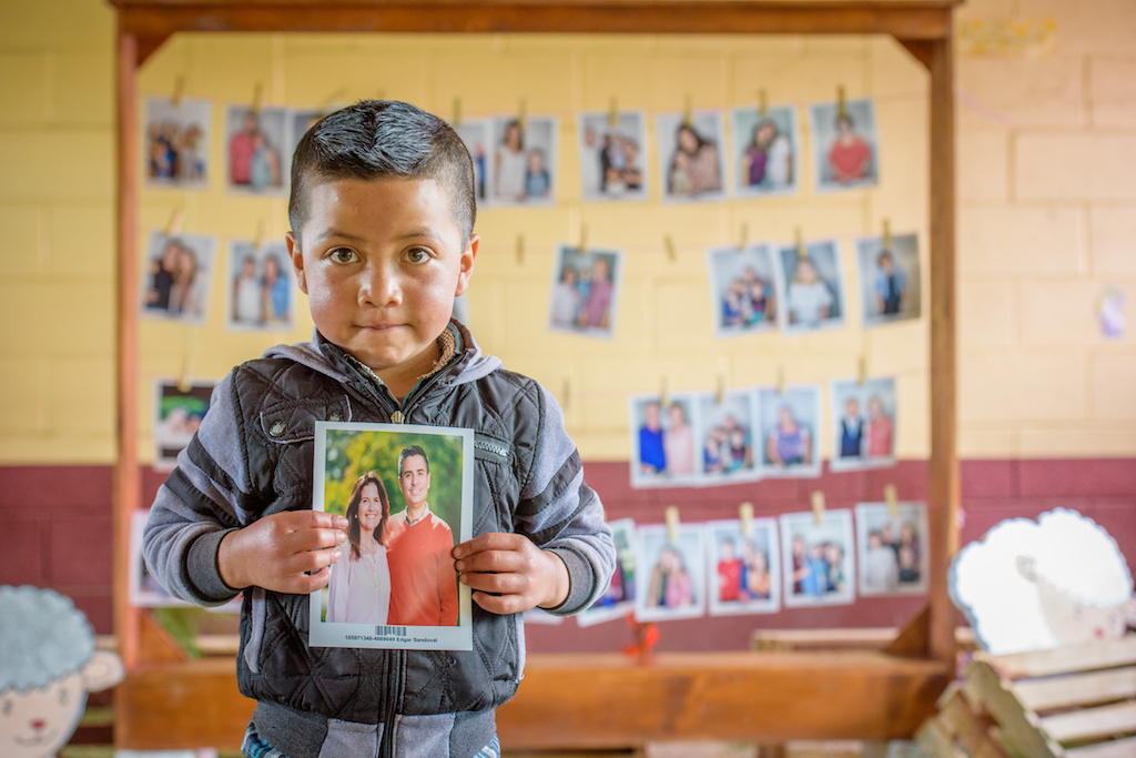 Six-year-old Wuilmer Garcia Tomas of Guatemala holds a picture of his sponsor, World Vision U.S. President Edgar Sandoval Sr., pictured with his wife, Leiza Sandoval. (©2019 World Vision/photo by Laura Reinhardt)